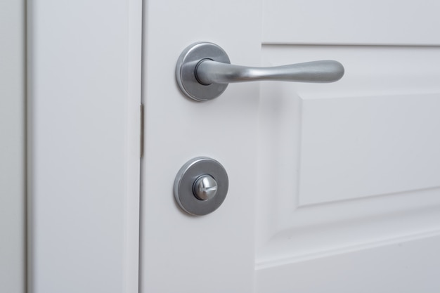 Szczegół biały drzwi wewnętrzne z chromowaną klamką