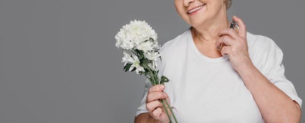 Szczegół buźka kobieta trzyma perfumy