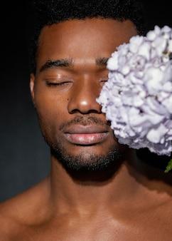 Szczegół ekspresyjny mężczyzna pozowanie z kwiatami