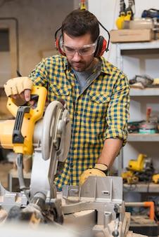 Szczegół fachowy męski pracownik używa saw w warsztacie