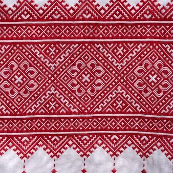 Szczegół haftowanego ornamentu z czerwonymi nitkami na białej tkaninie, ukraiński haft ludowy, z bliska. ubrania narodowe ukrainy