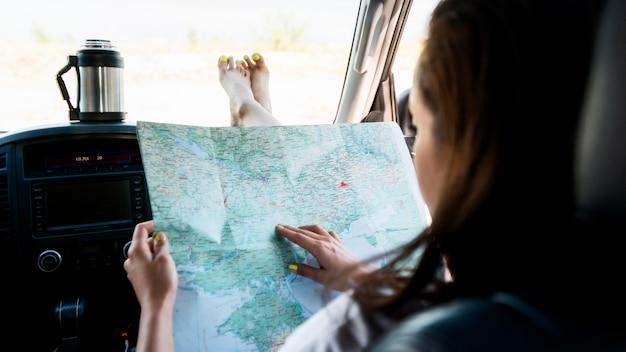 Szczegół kobieta sprawdzanie mapy wewnątrz samochodu