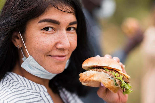 Szczegół kobieta trzyma smacznego burgera