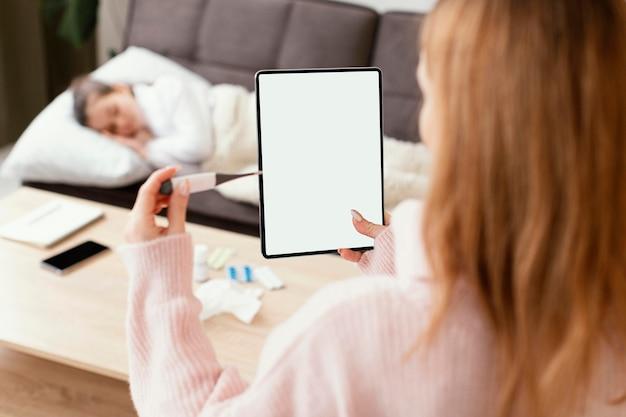 Szczegół kobieta trzyma tabletkę i termometr