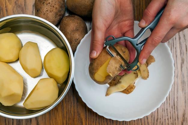 Szczegół kobieta wręcza strugać świeżego żółtego gruli z kuchenną obieraczką, karmowego przygotowania pojęcie.