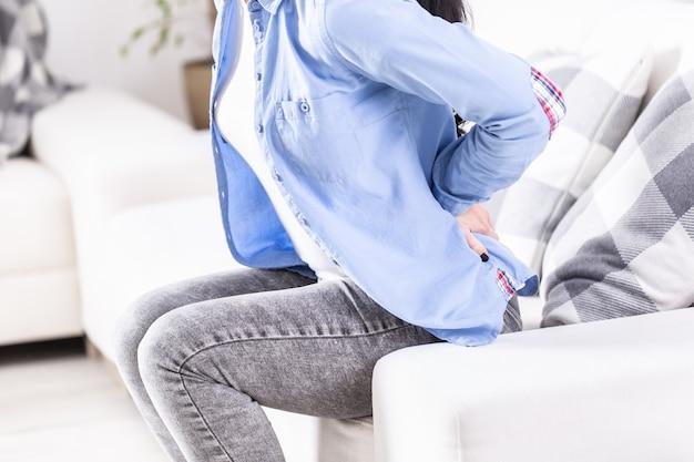 Szczegół kobiety siedzącej na kanapie, trzymającej ból w dolnej części pleców.