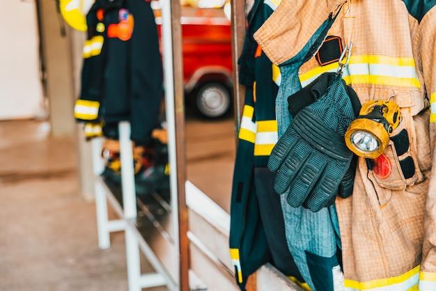Szczegół kombinezonu strażaka przygotowanego do akcji obok materiału w celu bezpiecznego gaszenia pożarów.