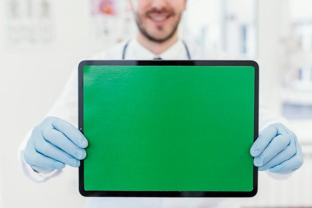 Szczegół lekarz trzymając tabletkę