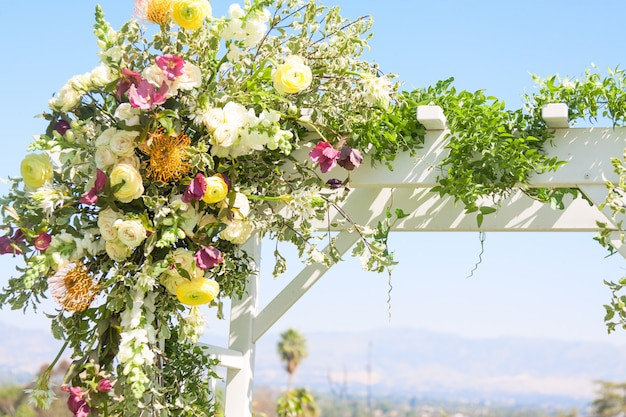 Szczegół łuku ślubnego, ozdobiony kwiatami.