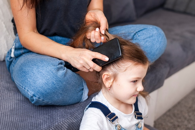 Szczegół matka stylizuje włosy córek