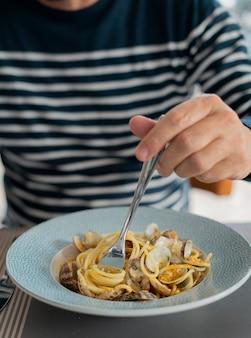 Szczegół męskiej dłoni jedzenie makaronu spaghetti z małżami i barwena, dania kuchni śródziemnomorskiej