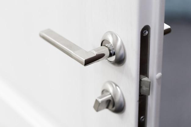 Szczegół metaliczna gałeczka na białym drzwiowym horyzontalnym