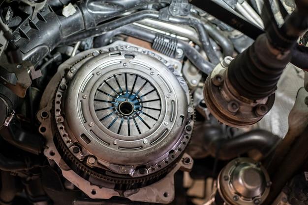Szczegół montażu sprzęgła samochodowego w warsztacie, silnik naprawy samochodu