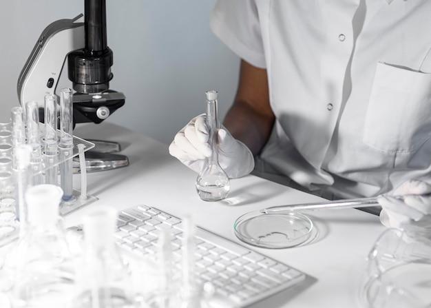 Szczegół naukowiec trzymając naczynia szklane