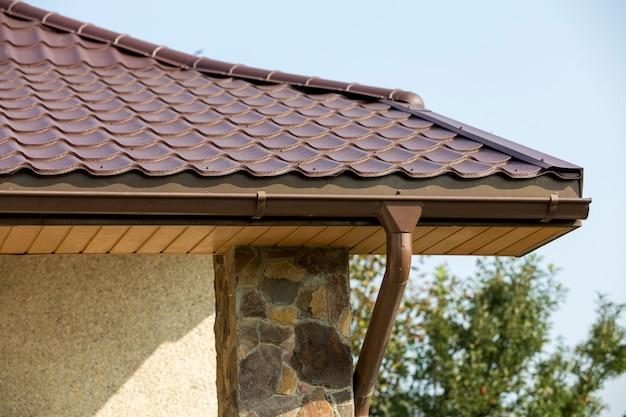 Szczegół nowego nowoczesnego narożnego domku ze ścianami ozdobionymi sztukaterią naturalnymi kamieniami, brązowym gontowym dachem i systemem rur deszczowych na niebieskim niebie. nieruchomości