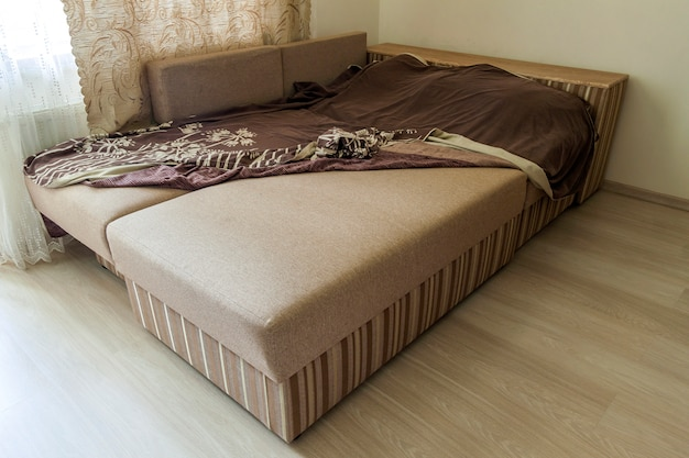 Szczegół nowożytna beżowa textured kanapa w salonie na drewnianej laminatowej parkietowej podłoga.
