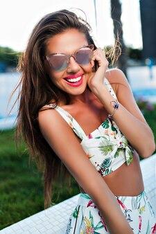 Szczegół portret atrakcyjna brunetka dziewczyna z długimi włosami pozowanie w mieście. ona uśmiecha się do kamery.