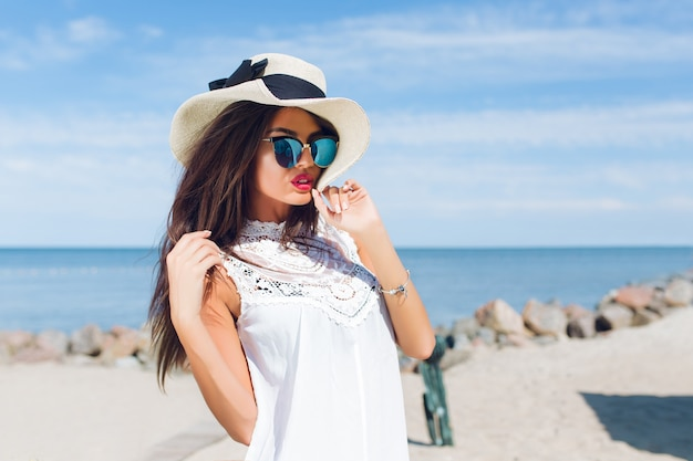 Szczegół portret atrakcyjna brunetka dziewczyna z długimi włosami stojąc na plaży w pobliżu morza. dotyka włosów i patrzy w dal.