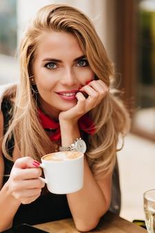 Szczegół portret atrakcyjnej młodej kobiety o ciemnoniebieskich oczach podpierając twarz ręką i uśmiechając się. pełen wdzięku dama trzyma filiżankę herbaty pozowanie podczas kolacji w kawiarni.