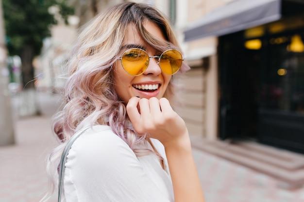 Szczegół portret atrakcyjnej, radosnej dziewczyny z niesamowitym uśmiechem nosi stylowe żółte okulary przeciwsłoneczne i białą koszulę