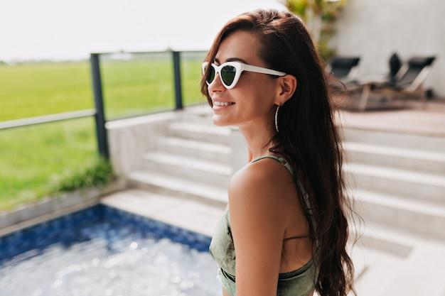Szczegół portret atrakcyjnej szczęśliwej uśmiechniętej kobiety w okularach i stroju kąpielowym pozowanie podczas sesji zdjęciowej przez zielone pole i basen. dziewczyna relaks w ośrodku spa w dobry słoneczny dzień