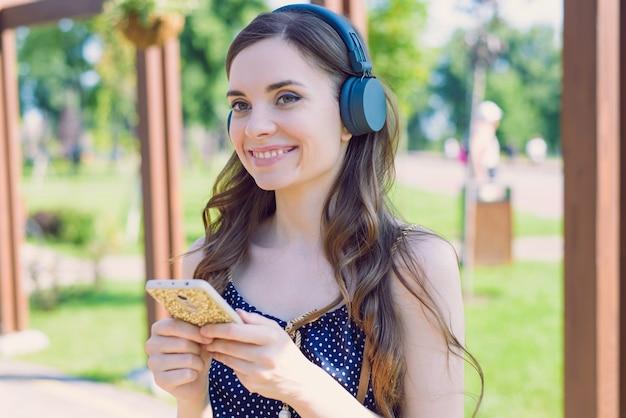 Szczegół portret atrakcyjny podekscytowany wesoły optymistyczny miły model studenta trzymającego za pomocą odtwarzacza gadżetów telefonicznych z muzyką pop w rękach o promiennym wyglądzie