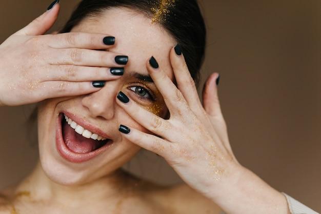 Szczegół portret białej młodej damy żartobliwie pozowanie. radosna dziewczyna z czarnym manicure śmiejąc się