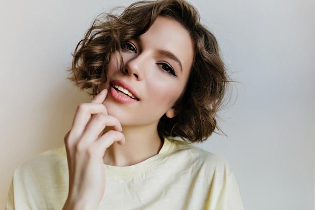 Szczegół portret białej zamyślonej dziewczyny z delikatnie uśmiechem. zdjęcie uroczej kobiety kaukaski z krótką fryzurą na białym tle na jasnej ścianie.