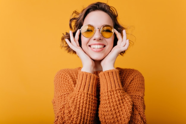 Szczegół portret blady kaukaski dziewczyna z pięknym uśmiechem. zdjęcie zrelaksowanej europejki nosi okrągłe żółte okulary przeciwsłoneczne.