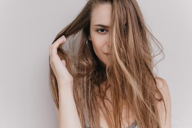 Szczegół portret ciemnooka dziewczyna na białym tle. kryty ujęcie uroczej europejskiej damy bawiącej się brązowymi włosami.