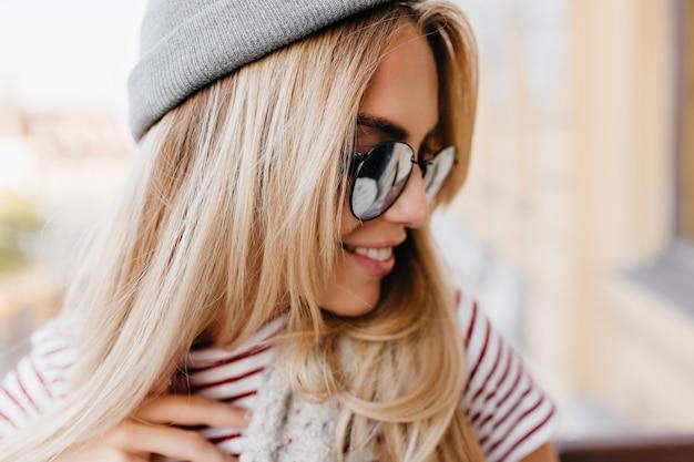 Szczegół portret czarujący jasnowłosy modelka odwracając się z ładnym uśmiechem