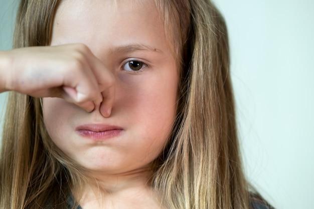Szczegół portret dziewczynki z długimi włosami, trzymając nos palcami wstręt.