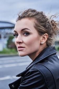 Szczegół portret dziewczyny modelka w czarnej kurtce z makijażem wygląda w dal