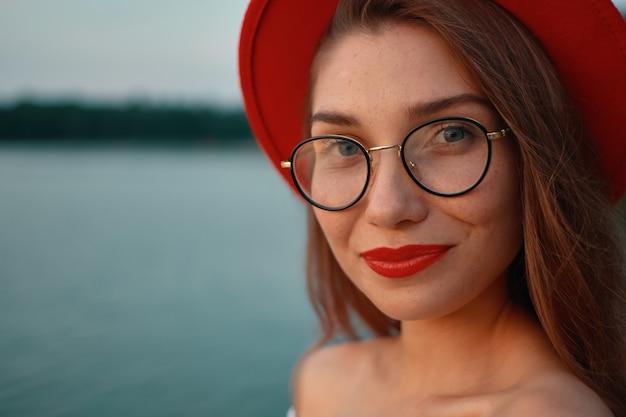 Szczegół portret dziewczyny z czerwonymi ustami, okulary i kapelusz