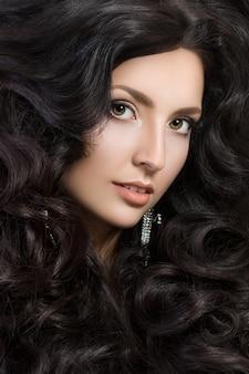Szczegół portret eleganckiej kobiety z pięknymi czarnymi włosami. piękna dziewczyna z idealną skórą. makijaż twarzy.