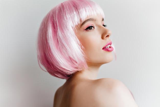 Szczegół portret eleganckiej młodej kobiety w różowej peruce odwracając się z zainteresowaniem. niesamowita dziewczynka kaukaski z krótkimi prostymi włosami, pozowanie na jasnej ścianie.