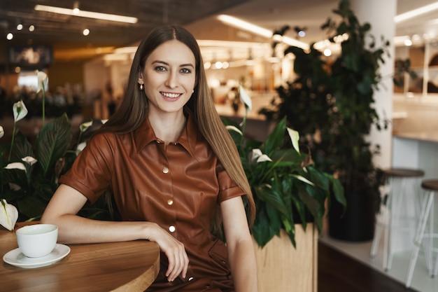 Szczegół portret eleganckiej uroczej młodej kobiety, opierając się na stoliku w kawiarni.