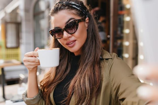 Szczegół portret hiszpanin młoda kobieta z wstążką, ciesząc się kawą w jesienny dzień
