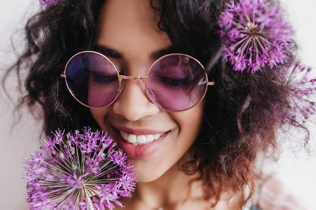Szczegół portret inspirowanej czarnej dziewczyny cieszącej się kwiatami. kryty zdjęcie uśmiechniętej fascynującej kobiety trzymającej allium.