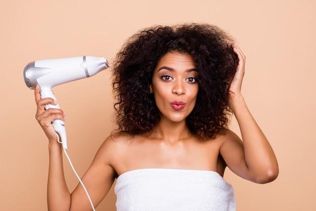 Szczegół portret kobiecej dziewczyny falowane włosy za pomocą suszarki elektrycznej