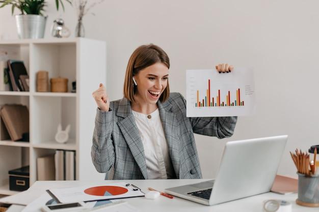 Szczegół portret kobiety biznesu szczęśliwy w stylowym stroju. dziewczyna w świetnym humorze pokazuje wykres przez skype.