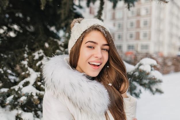 Szczegół portret kobiety o niebieskich oczach ze śniegiem we włosach, ciesząc się szczęśliwy czas zimowy. plenerowe zdjęcie zmysłowej blondynki ze szczerym uśmiechem stojącej na ulicy obok zielonego świerku.