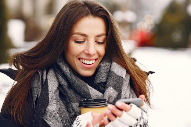 Szczegół portret kobiety w czarnej kurtce picia kawy i trzymając smartfon