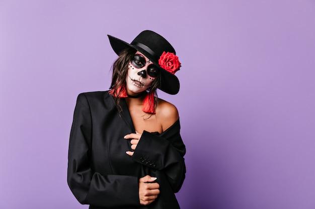 Szczegół portret kobiety z namiętnym wyglądem. model w czarnym kapeluszu z różą pozuje na liliowej ścianie.