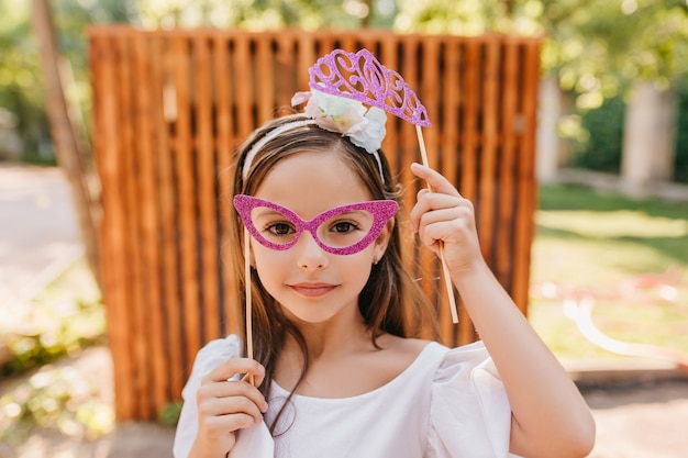 Szczegół portret małej modnej damy w różowe okulary i białą wstążką w ciemnych włosach. zewnątrz zdjęcie dziewczyny z zabawkami blask korony pozuje przed drewnianym płotem.