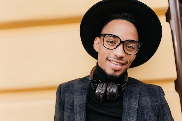 Szczegół portret męski model o ciemnej skórze wyrażający pozytywne emocje. zewnątrz zdjęcie uroczego czarnego mężczyzny idącego ze słuchawkami w weekend.