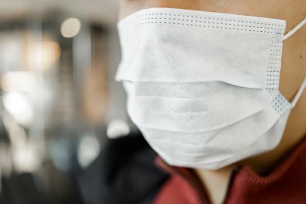 Szczegół portret mężczyzny noszącego maskę chirurgiczną, aby zapobiec wirusowi