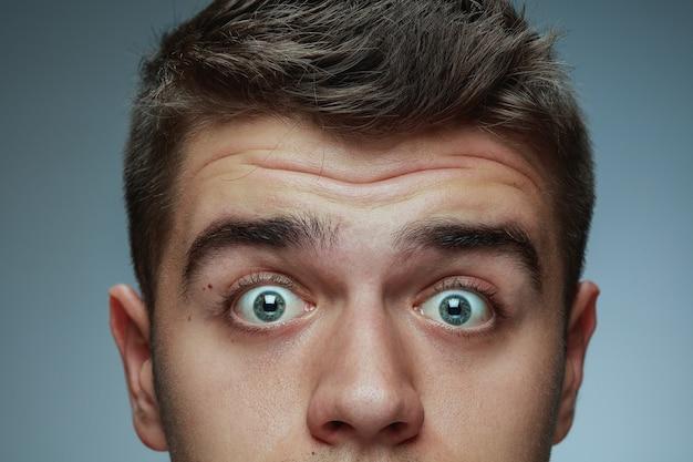 Szczegół portret młodego człowieka na białym tle na szarym tle studio. twarz mężczyzny rasy kaukaskiej i niebieskie oczy. pojęcie męskiego zdrowia i urody, samoopieki, pielęgnacji ciała i skóry. wygląda na zdziwionego.