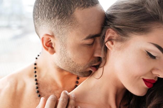 Szczegół portret młodego mężczyzny całującego szyję kobiety w pomieszczeniu