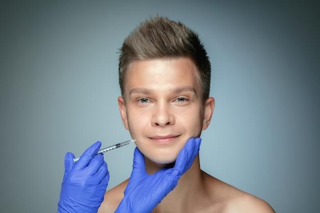 Szczegół portret młodego mężczyzny na białym tle na szarej ścianie. wypełnienie zabiegu operacyjnego ust i kości policzkowych. koncepcja zdrowia i urody mężczyzn, kosmetologii, pielęgnacji ciała i skóry. przeciw starzeniu.